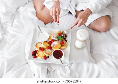 Girl in bed in a hotel room enjoys breakfast with cheese pan cakes served with red strawberry jam, raspberries and wild berries