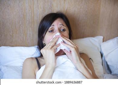 Girl in bed, Sinus pain, sinus pressure, sinusitis. Sad woman holding her nose and head because sinus pain. Sinus ache causing very paintful headache.
