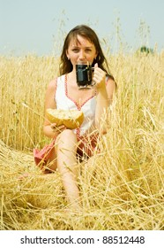 Girl  with beer and bread  at wheat field