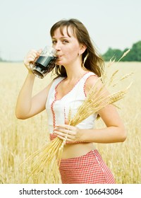 Girl  with beer at cereals field in summer