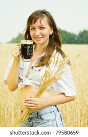Girl  with beer and wheat ears  at cereals field