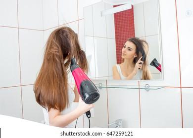 girl before the mirror dries hair