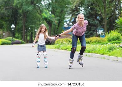 Girl beginner in roller skates with mom