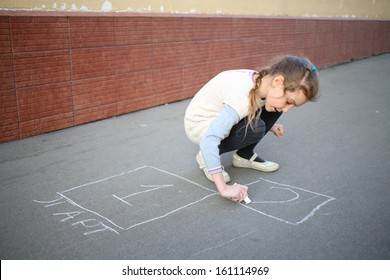 The girl begins to draw hopscotch on the pavement on the street