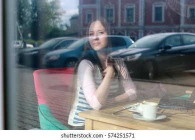 girl behind glass in cafe