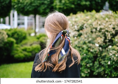 Girl from behind in park. Beautiful handkerchief with colored patterns tied on wavy hair, the wind blows. For the blog. Green background