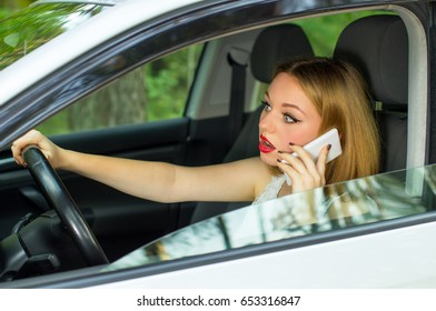 The girl behind the wheel of a car talking on the phone, scared and looks in front of