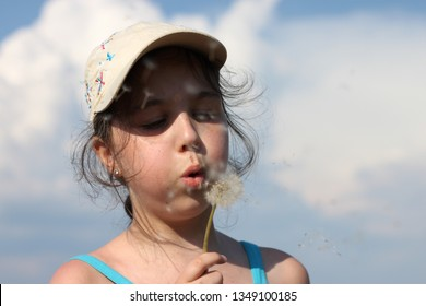A girl in a beige cap with butterflies and a sharp shadow on her face, blowing on a white dandelion against the blue sky on a bright Sunny day