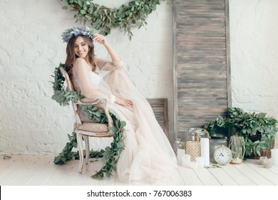 A girl in a beige peignoir, with a wreath of flowers on her head, poses in the studio loft, fine art wedding style