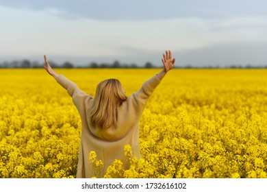A girl in a beige warm jacket in a yellow field of blooming rapeseed with her arms outstretched to the sky.
