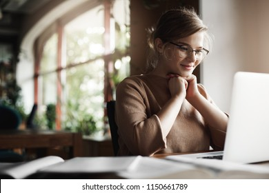 Girl being pleased with great job and positive result of work, sitting in quiet and cozy cafe, leaning head on hands and smiling broadly with satisfied expression at laptop, finishing project in time