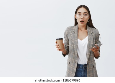 Girl being thrilled retelling story from phonecall to friend. Emotive stylish female student in jacket and glasses, holding smartphone and cup of coffee, talking at camera with amazement