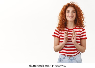 Girl believed luck her side. Optimistic good-looking redhead curly girlfriend praying cross fingers faith anticipate important results standing excited smiling making wish hopeful, white background