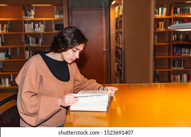 Girl bent over book sitting in library alone