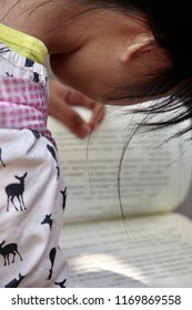 A girl is bent over to read a Chinese book