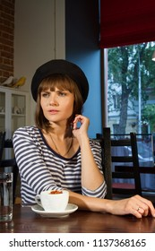 girl in a beret sits at a table in a cafe