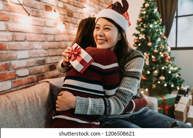 girl best friends celebrating christmas together. young ladies exchanging gifts at home and feel thankful hugging. love friendship on xmas concept.