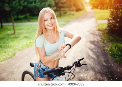 Girl bicycle with fitness bracelet activity tracker, smart clock. Concept sports and technology, pulse measurement, speed control application, health lifestyle, walks in park and life.