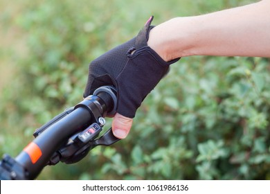 A girl in a bicycle gloves holds her hand on the handlebars, switches speeds.