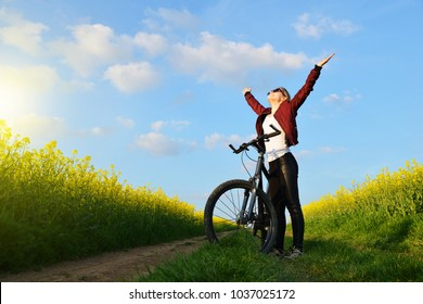 Girl with bicycle on a dirt road in rapeseed field. Healthy lifestyle concept.