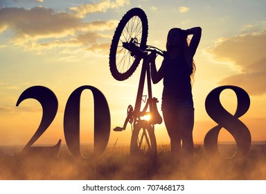 Girl with bicycle at sunset. Forward to the New Year 2018.