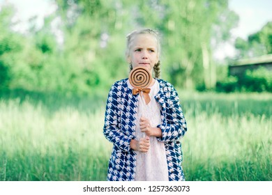 Girl with a big candy on a stick in the summer in a clearing