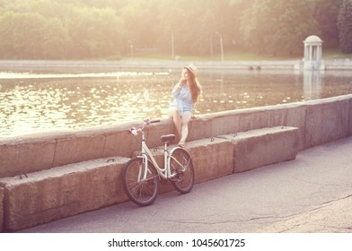 Girl with bike in the city in sunrise time. copyspace