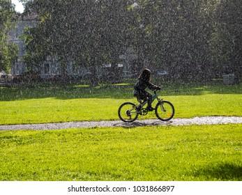 Girl bikes in urban park with rain and sunshine