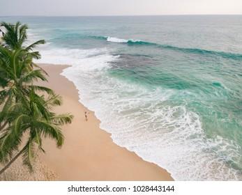 Girl in bikini enjoy summer day near ocean. Vacation in Sri Lanka. Photo from drone