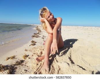 Girl in a bikini on the beach near the sea