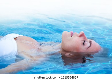 Girl in bikini relaxing floating in blue water of swimming pool