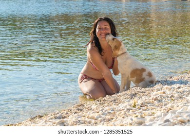 a girl in bikini very happy with her dog. Also her puppy loves her. They are palying at the beach.