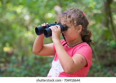 Girl with a binocular in the forest