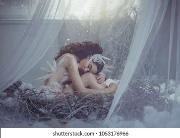 The girl bird sits in her nest, timidly bowing her head and embracing her legs. A nest in a fairy-tale house, near the window from which the light is pouring and the snow gently slides. Art photo