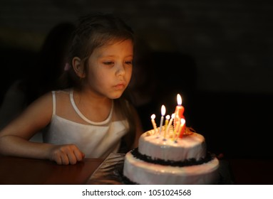 girl with birthday cake blowing caldles in darkness