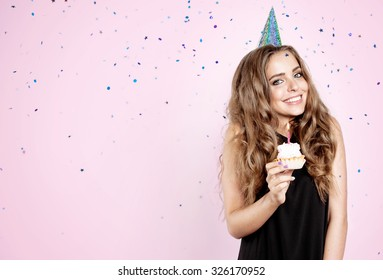 Girl with birthday cake on a pink background and confetti