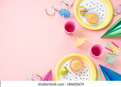 Girl birthday decorations. Pink table setting from above with muffins, drinks and party gadgets. Background layout with free text space.