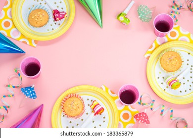Girl birthday pink table setting from above with muffins, drinks and party gadgets. Background layout with free text space.