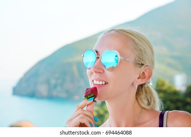 girl bites a ripe strawberry by the sea