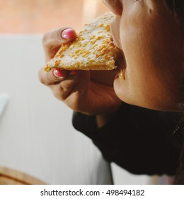 Girl biting slice of pizza. Copy space. Side view.