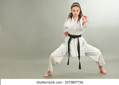 Girl with black belt in karate pose
