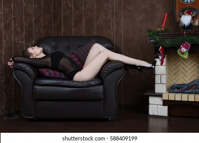 Girl in a black body is lying on the leather chair