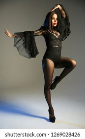 the girl in the black bodysuit is dancing on white background. girl in high heels in black pantyhose with hearts and beautiful bodysuit is posing on cyclorama