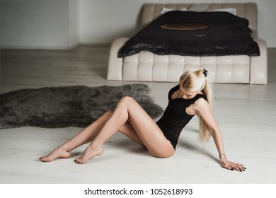 Girl in black bodysuit posing on the floor in the bedroom.