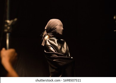 girl in a black cape on a black background, backstage