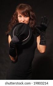 The girl in black clothes on a black background with a hat