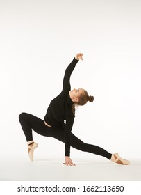 A girl in black clothes and Pointe shoes on a white isolated background performs dance and ballet poses and movements. The concept of theatre and performing arts.