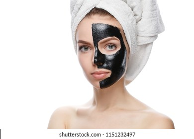 girl with black cosmetic mask on face and head wrapped in towel, mask made at home isolated on white background