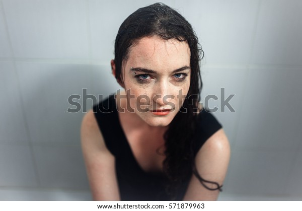 girl in a black dress in the bath under the shower