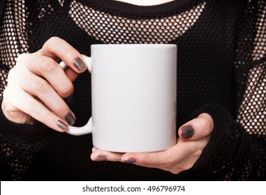 Girl in black dress is holding white mug in hands. Mockup for Halloween gifts design.